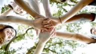 Vielfältige ehrenamtliche Gruppe mit Händen im Huddle vor Community-Projekt