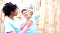Diverse volunteers building home for charitable organization