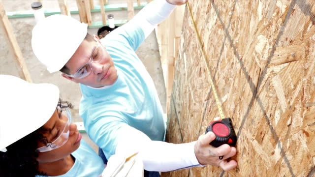 Diverse volunteers measure plywood on home being built for charity