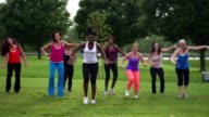 Diverse women wearing colorful clothing doing Zumba in suburban park
