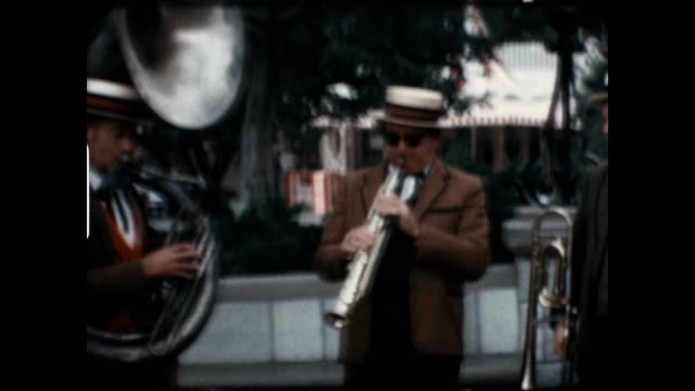 A Dixieland jazz band plays for the crowd Disneyland in the 1960's