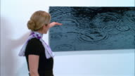 Docent looking at and explaining photograph of rippled water to two men in contemporary art gallery