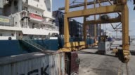 Dock workers stand beside an AP Moeller Maersk A/S shipping container as it is loaded onto cargo vessel Santa Bettina operated by Reederei ClausPeter...