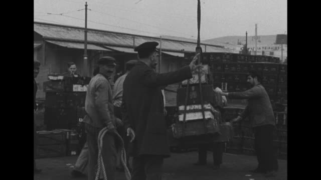 Dockworkers loading cargo into flatbed trucks / crane lowers cargo / large of group of bombs awaits loading / Note exact month/day not known