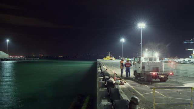 TL WS Dockworkers tying up container ship as it arrives and night turns to dawn at Ports of Auckland/ Auckland, New Zealand