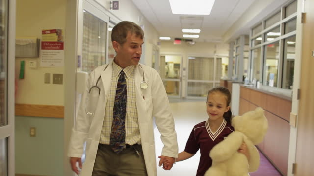 MS DS Doctor and girl (8-9) holding teddy bear walking through hospital corridor / Portland, Maine, USA