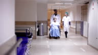 Doctor and nurse is driving patient on wheelchair along corridor