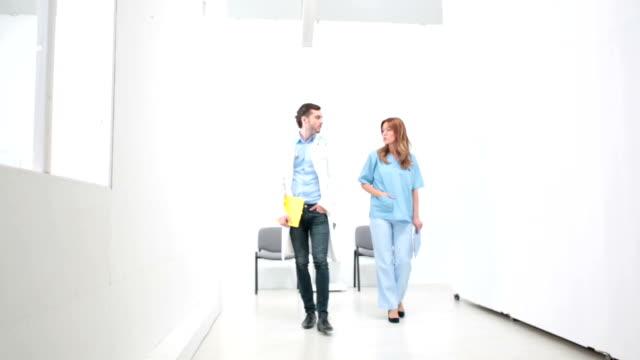 HD: Doctor and nurse walking in hospital corridor.