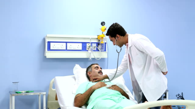 Doctor checking a patient in hospital, Delhi, India