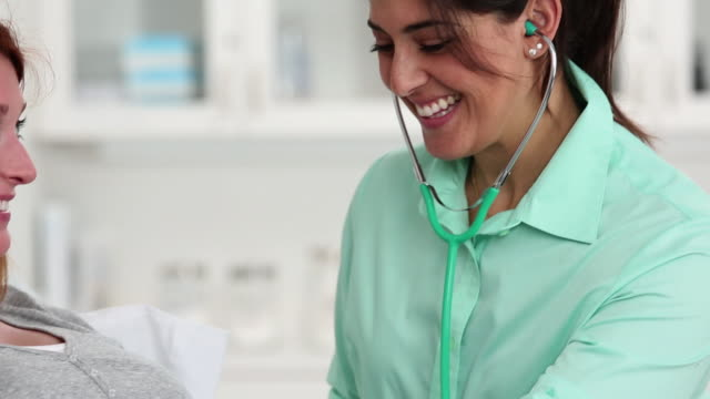 CU TU Doctor Checking Baby's Pulse on Pregnant Woman's Abdomen / Richmond, Virginia, USA
