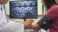 Läkare kontrollera blodtrycket av patienten vid skrivbord i sjukhus, Slow motion