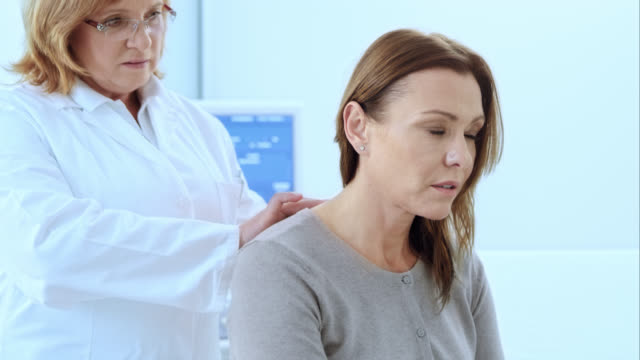 Doctor checking the female patients spine