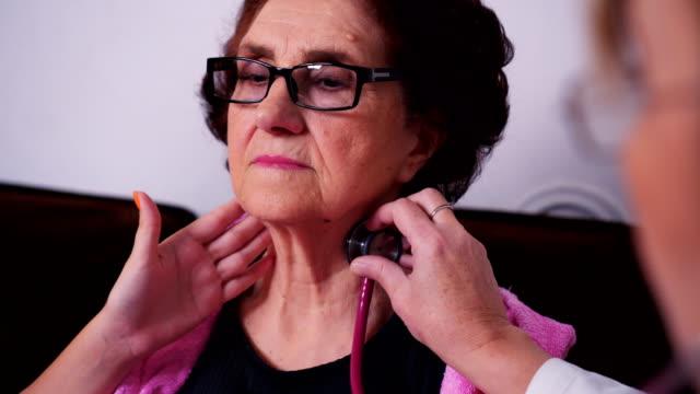 Läkare kontrollerar villkora av äldre patient