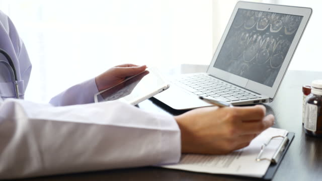 Doctor diagnostic and Writing Prescription on Clipboard with Digital Tablet and examining X-ray image