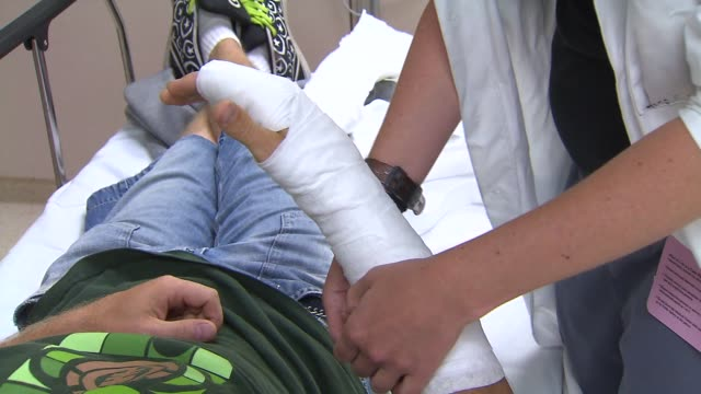 Doctor Examines Arm Cast In ER