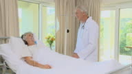 MS DS Doctor examing patient in coma lying on bed in hospital room / Cape Town, Western Cape, South Africa