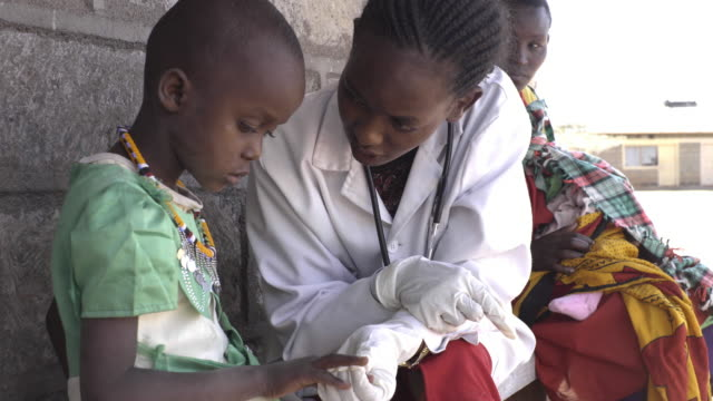 Doctor examining child patient at clinic. Kenya, Africa