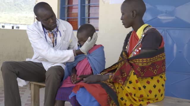 Doctor examining child patient. Kenya, Africa.