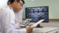 Läkaren undersöker MRI File på Digital tablett på sjukhuset office