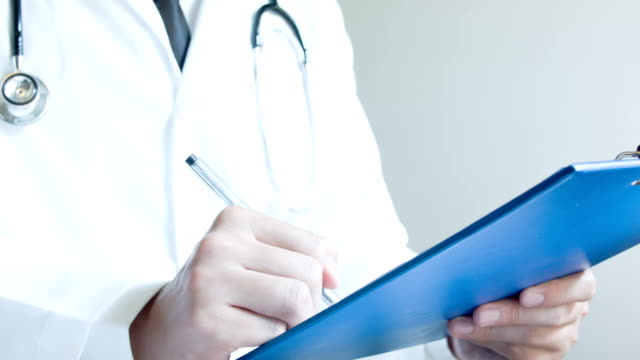 Arzt im medizinischen Formular ausfüllen