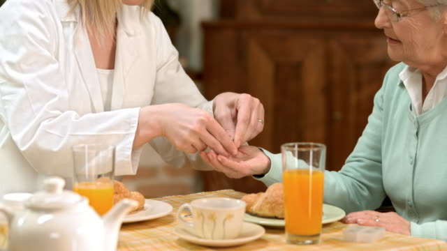 PAN Arzt geben eine Tablette auf ältere Frau beim Frühstück