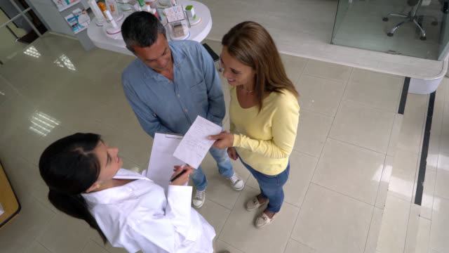 Doctor handing a prescription to a couple at a drugstore