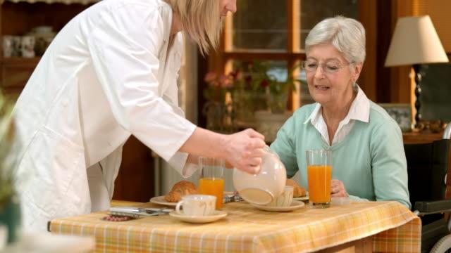 TU Doctor having tea with her senior female patient
