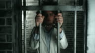 Doctor holding prison bars at prison cell