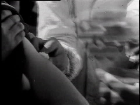 doctor injecting patient in arm / patient holding cotton to injected area