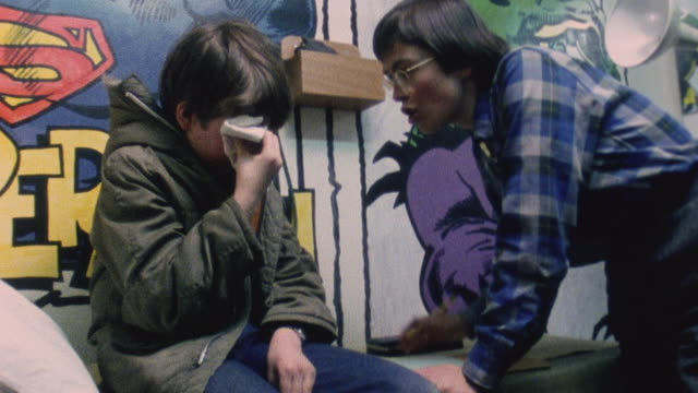 1983 MONTAGE Doctor Iona Heath examines a young patient with an eye injury / London, England