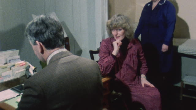 1983 MONTAGE Doctor Keith Lister chatting with patient and taking her blood pressure while the patient's child plays quietly on the floor / London, England