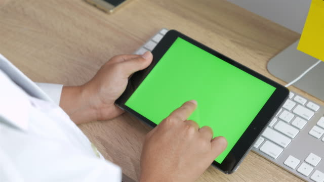 Doctor look at chroma key digital tablet