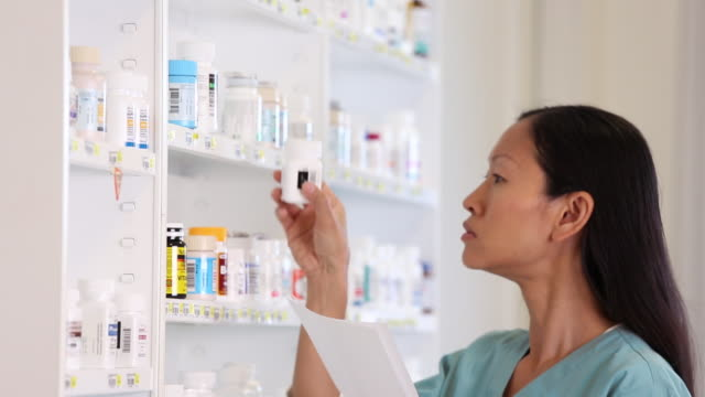 MS TD Doctor Looking at Medication Bottles in Hospital Pharmacy / Richmond, Virginia, USA