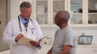 MS Doctor Looking at Records, Talking to Senior Patient in Medical Office / Richmond, Virginia, USA