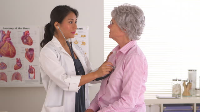 doctor performing a basic checkup on mature patient