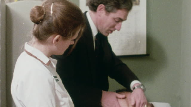 1982 MS Doctor performing prenatal examination and ultrasound on expectant mother / Oxford, Oxfordshire, England