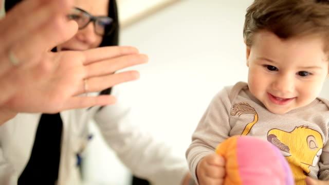 Läkare leker med en lekfull liten pojke på sjukhuset