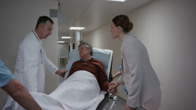 Doctor reassuring the daughter and taking her father to the examining room