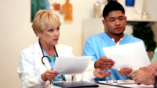 Doctor sharing paperwork with team of healthcare professionals