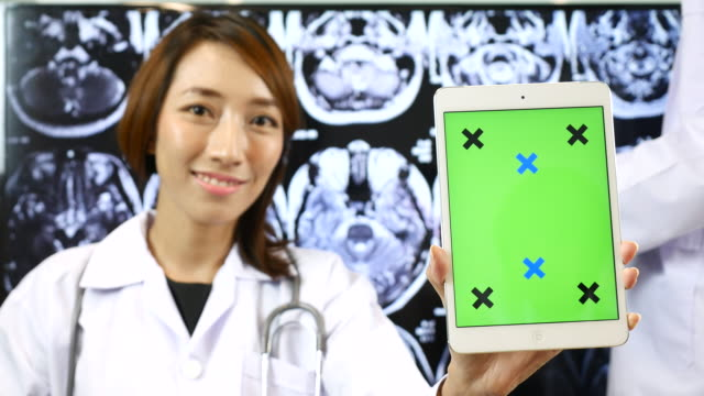 Doctor showing green screen of Digital tablet on Brain X-ray image bachground, Chroma Key