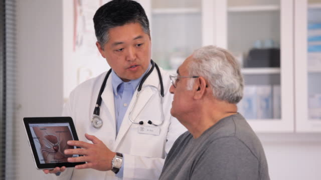 MS PAN Doctor Showing Prostate Diagram on Tablet Computer to Senior Patient / Richmond, Virginia, USA