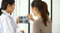 Arzt zeigen ihre Patienten Röntgen auf digitale Tablet im Untersuchungsraum in Krankenhäusern