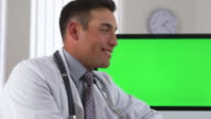 doctor smiling with green screen on computer in background