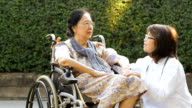 Doctor take caring old woman on wheelchair
