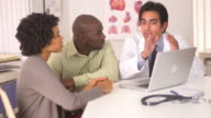 doctor talking to couple with laptop computer