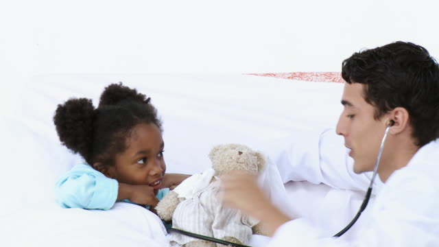 MS Doctor talking to girl (4-5) lying in hospital bed, girl examining teddy bear with stethoscope / Cape Town, Western Cape, South Africa