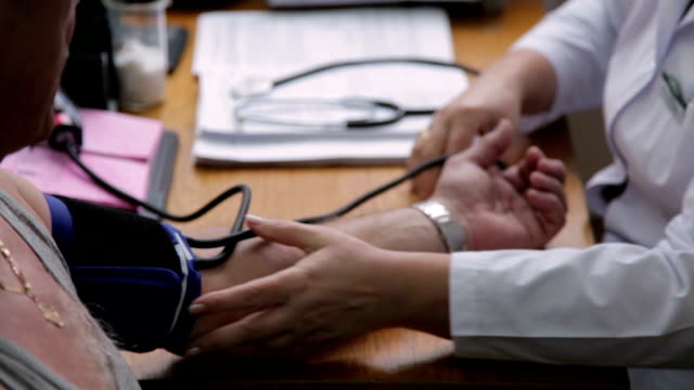 Doctor using blood pressure gauge to checking blood pressure