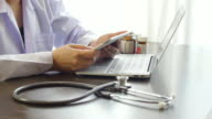 Doctor using on Tablet PC for Examining with stethoscope