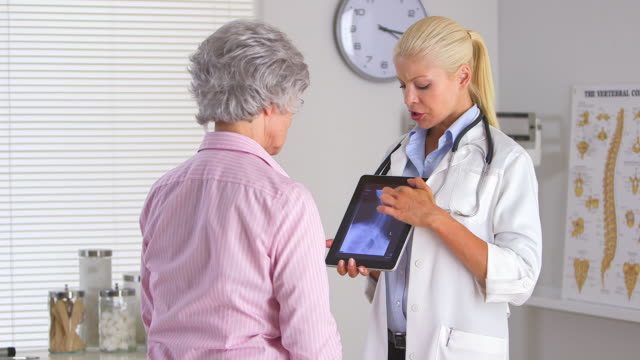 Doctor using tablet computer to display x ray for elderly woman patient