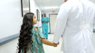 Doctor walks little girl down hospital hallway